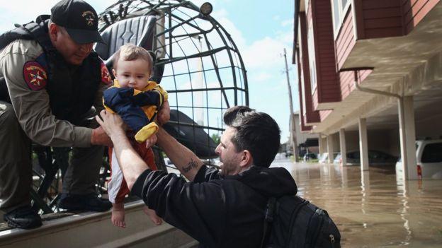 Un rescatista le entrega un bebé a un hombre que está hundido hasta la mitad del cuerpo por una inundación.
