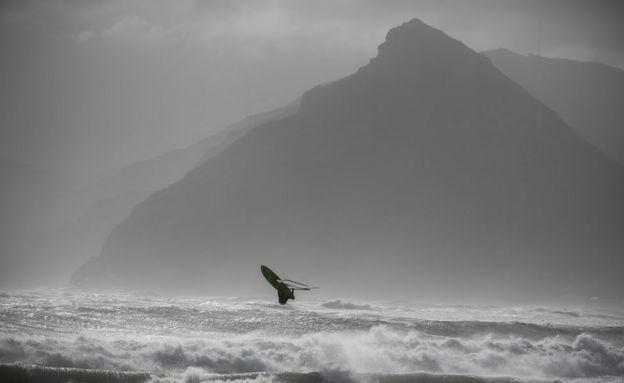 Windsurfer Jake Kolnik sails during a storm in Cape Town, South Africa 07 June 2017. A powerful storm with gale force winds, heavy rain and seas in excess of 10 meters lashed the peninsula causing damage to property and vegetation.