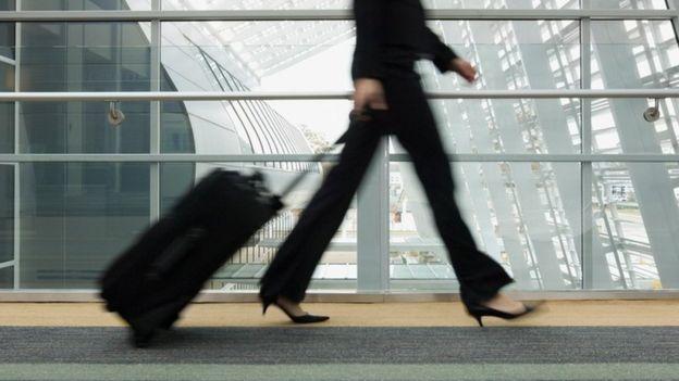 Una mujer arrastrando una maleta por un aeropuerto