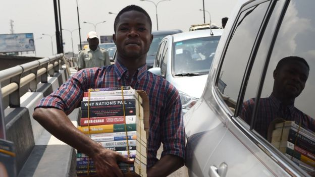 A street vendor sells books on a busy road in Lagos, Nigeria.