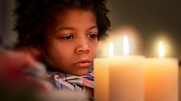 Niño mirando las llamas de velas