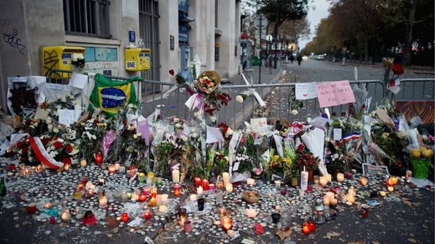 Flowers, candles and tributes cover the pavement near the scene of Friday's Bataclan theatre terrorist attack on November 15, 2015 in Paris, France.