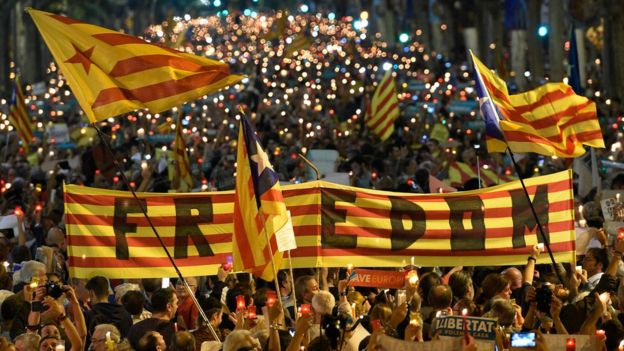 People attend a candle-lit demonstration in Barcelona against the arrest of two Catalan separatist leaders on October 17, 2017