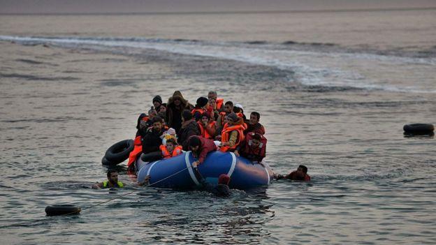 una barca llena de refugiados llega a la costa.