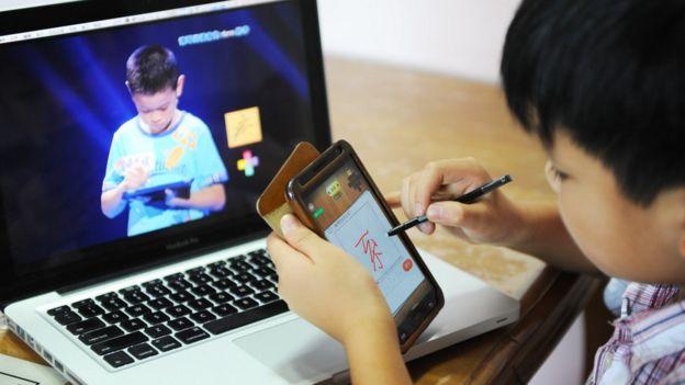 Un niño con un teléfono celular en China