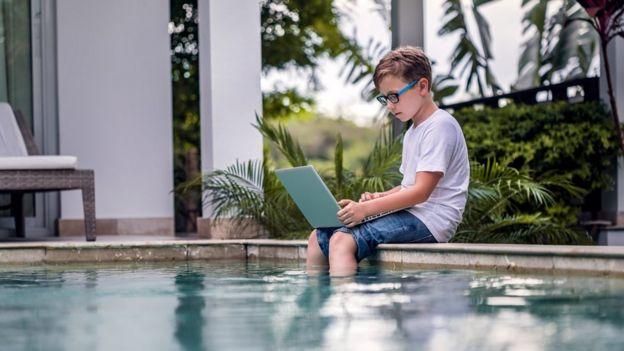Niño con una laptop en una piscina