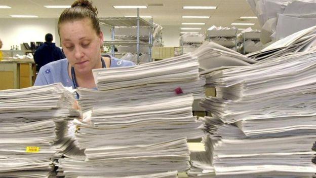 Una mujer detrás de varias pilas de papeles