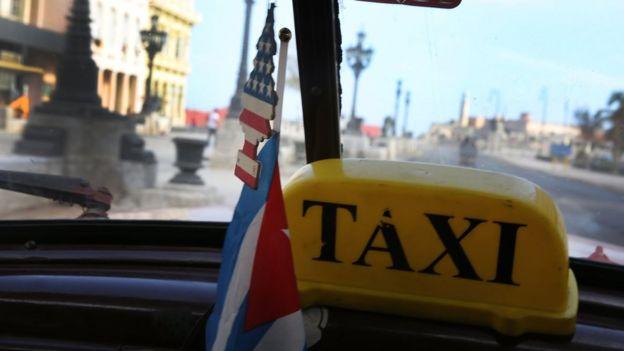 La vista desde dentro de un taxi en La Habana. El aromatizador que cuelga del espejo retrovisor es un arbolito con la bandera de Estados Unidos.