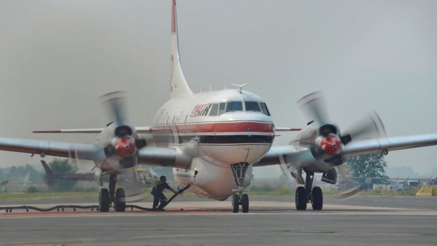 A ground crew fills a Conair airtanker with fire retardant at the Provincial Wildfire Coordination Centre at Kamloops Airport