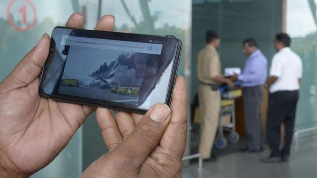 Un hombre sostiene un teléfono donde se ven imágenes del accidente del avión en cuestión