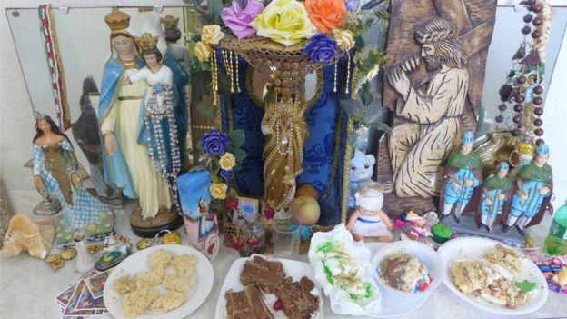 Sincretismo religioso em um pequeno altar mantido com oferendas na casa