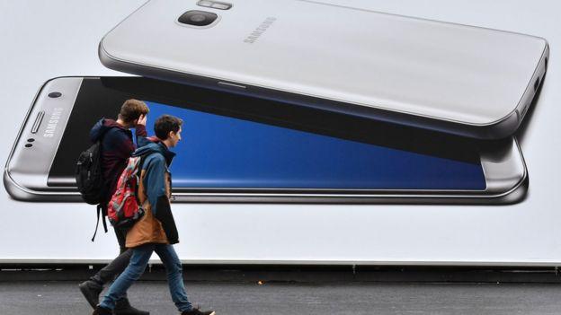 Dos jóvenes pasan frente a una propaganda de Samsung