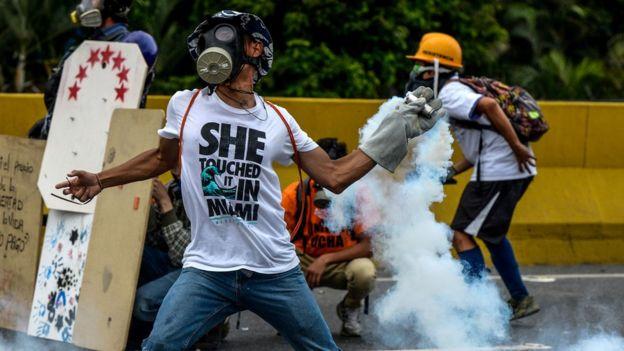 Manifestantes lanzan de vuelta bombas lacrimógenas a las fierzas de seguridad.