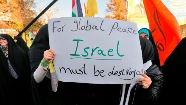 """Manifestantes con una pancarta que dice: """"Para la paz global, Israel debe ser destruida"""""""