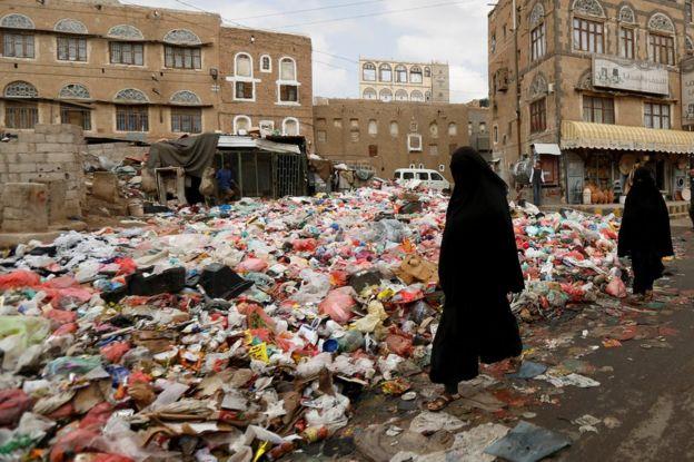 Mujeres caminan entre la basura acumulada en una calle de Saná, Yemen, el 8 de mayo de 2017.