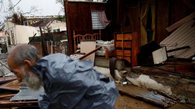 Homem em frente a casa sem paredes em Porto Rico.
