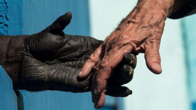Chimpanzé dando a mão a um humano
