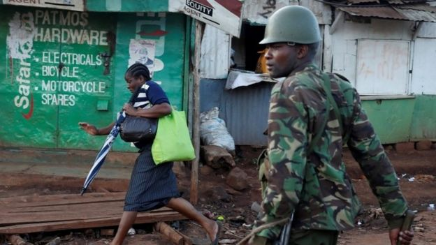 A woman runs in front of a policeman during clashes between opposition supporters and police in Kawangware slum in Nairobi (30 October 2017)
