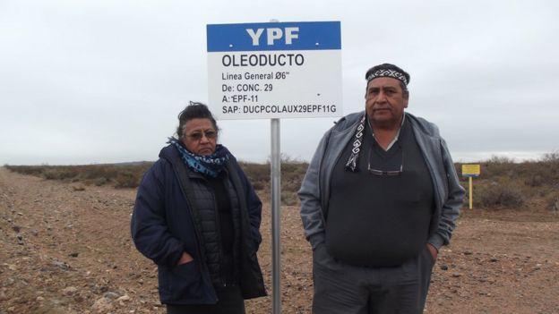 Josifa y Albino Campo ante un cartel de un oleoducto de YPF.