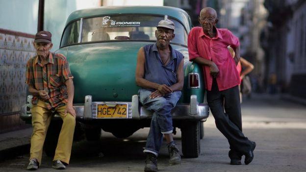 Tres hombres sobre un carro en La Habana.