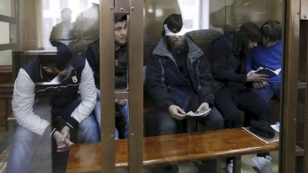 The five defendants in a glass cage in Moscow's court