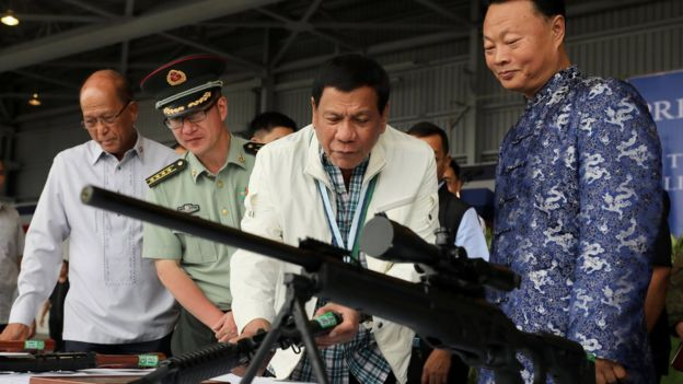 Philippine President Rodrigo Duterte (C) checking the scope of a Chinese-made CS/LR4A sniper rifle during the ceremonial handover of military weapons from China to the Philippines at the Clark Air Base in Pampanga province, Philippines, 28 June 2017