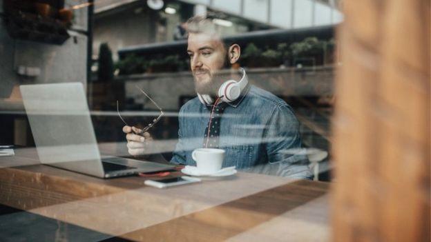 Un joven trabajando con su laptop en un café