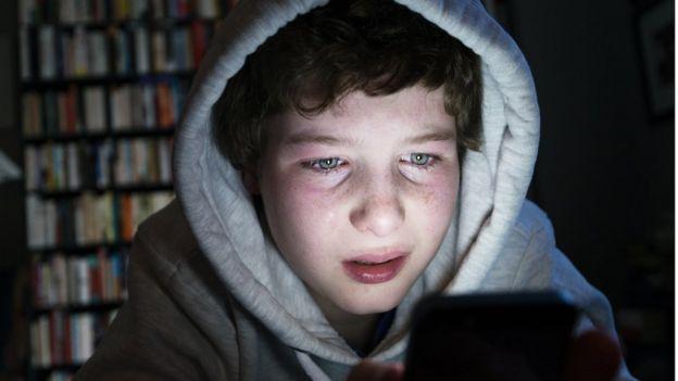 Niño ante el celular con cara de sufrimiento