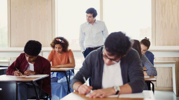 Un maestro inspecciona a unos alumnos tomando un examen en un salón de clases