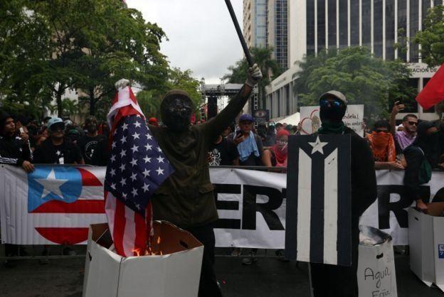 Hombres enmascarados prenden fuego la bandera de Estados Unidos.