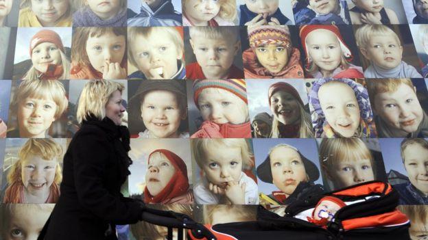 Una mujer pasa frente a un poster con rostros de niños en Islandia
