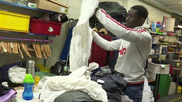Un hombre revisa ropa en una tienda de Oxfam.