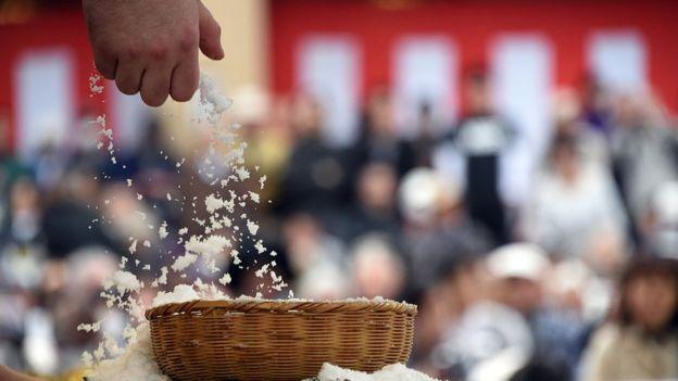 A wrestler grabs a handful of salt from a basket