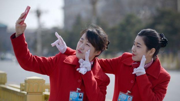 Mujeres chinas posando para un selfie con guantes.