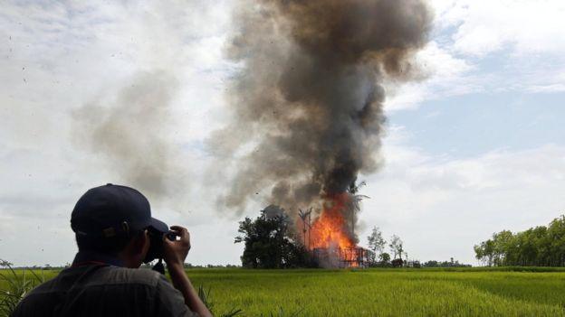 Journalist take photos of a burning house at the Gawdu Zara village in Maungdaw township, Rakhine State, western Myanmar, 7 September 2017