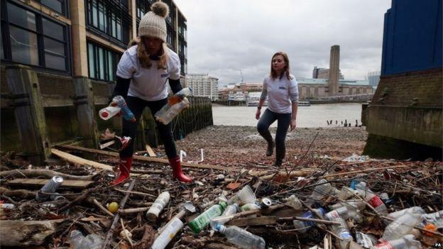 志愿者在伦敦泰晤士河畔捡塑料瓶并点数。