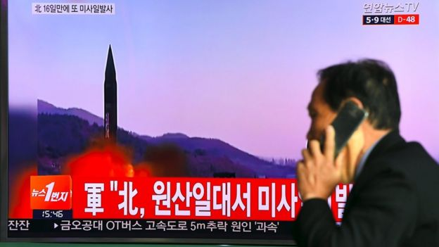 Man in Seoul walks past a TV screen showing file footage of North Korean missile launch on March 22, 2017