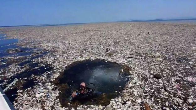 Homem mergulha em mar de lixo
