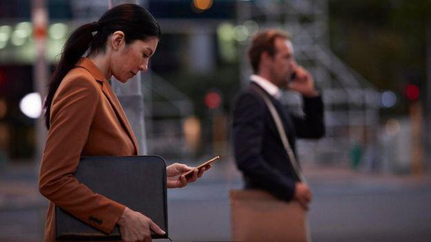 امرأة تنظر إلى هاتفها المحمول وهي تخرج من مقر العمل