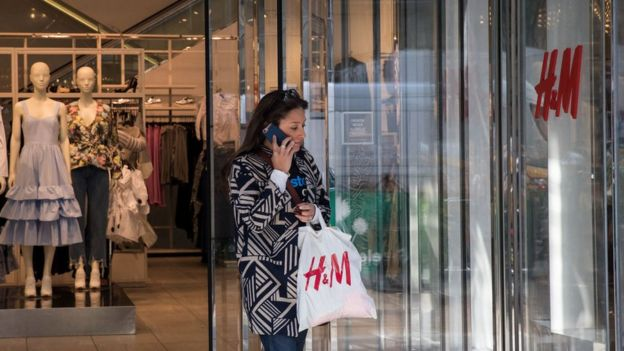 A woman leaves an H & M store.