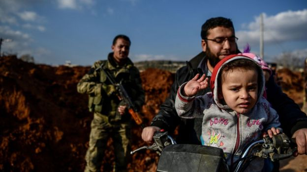 A Turkish-backed Syrian rebel fighter stands guard at a checkpoint as a family passes on motorbike in the Syrian town of Azaz on a road leading to Afrin, 1 February 2018