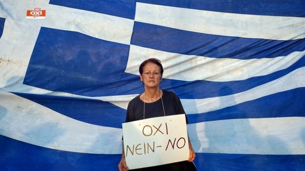 Woman protesting in front of the Greek flag
