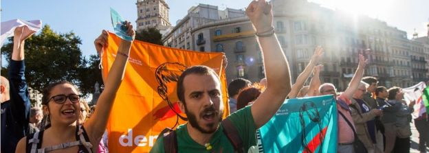 Protesters with 'democracy' flags chant outside the Catalan economy ministry