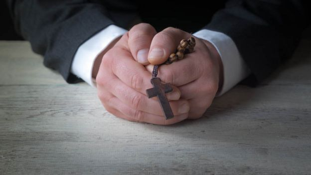 Man in suit with a crucifix