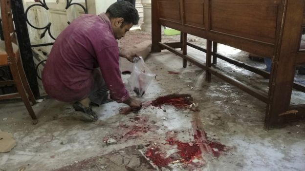A Christian employee at Cairo's Coptic Cathedral checks for damage from the blast after an explosion inside the cathedral in Cairo