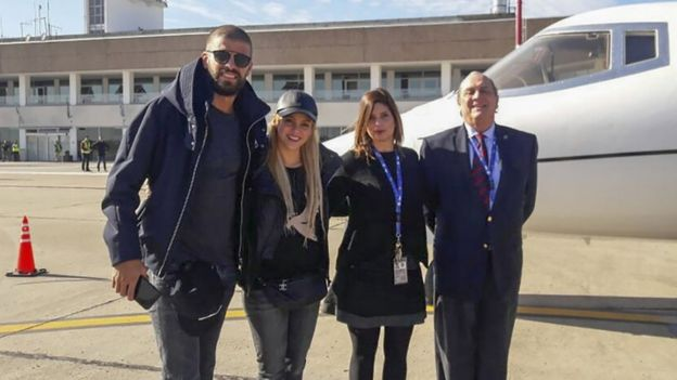 Gerard Piqué (left) alongside his wife, Shakira, and airport staff in Rosario