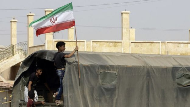 A Syrian teenager hoists an Iran flag aboard a truck carrying supplies to Deir Ezzor
