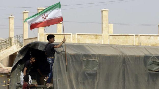 Un adolescente sirio enarbola una bandera de Irán a bordo de un camión que lleva provisiones a Deir Ezzor