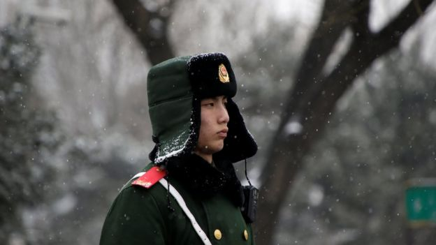 A paramilitary police officer stands guard during a snowfall ahead of a welcoming ceremony held by Chinese Premier Li Keqiang for the French Prime Minister Bernard Cazeneuve near Tiananmen Square in Beijing, China. February 21, 2017.