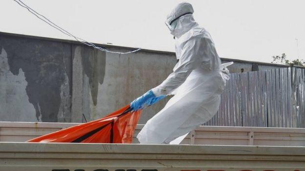 Mezar takımındaki bir Liberya sağlık çalışanı, Ebola kurbanının cesedini Monrovia'da kremasyona sürükledi (13 Ekim 2014)